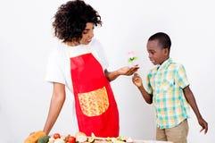 Petit garçon donnant une fleur à sa mère Photo stock
