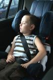 Petit garçon dormant dans le véhicule Photo stock