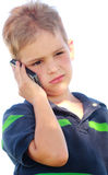 Petit garçon douteux au téléphone Photo stock