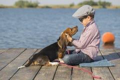 Petit garçon doux étreignant son chien Images stock