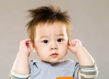 Petit garçon doux avec l'oreille de contact de main photographie stock libre de droits
