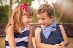 Petit garçon doux et une fille s'asseyant sur un banc en parc et Images libres de droits