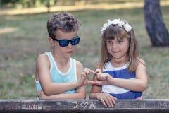 Petit garçon doux et une fille se tenant prêt le banc en parc Photographie stock