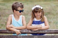 Petit garçon doux et une fille se tenant prêt le banc en parc Photo stock