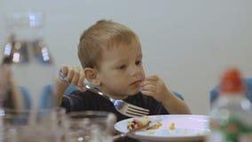 Petit garçon drôle avec de grands yeux mangeant le plat incompétent 4K banque de vidéos