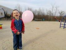 Petit garçon drôle avec le ballon rose, sourires Photos stock
