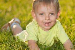 Petit garçon drôle se trouvant sur l'herbe verte photos libres de droits