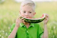 Petit garçon drôle d'enfant en bas âge avec les poils blonds mangeant la pastèque dehors Photos stock