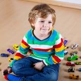 Petit garçon drôle jouant avec un bon nombre de voitures de jouet d'intérieur Photo stock
