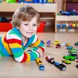 Petit garçon drôle jouant avec un bon nombre de voitures de jouet d'intérieur Images libres de droits