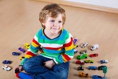 Petit garçon drôle jouant avec un bon nombre de voitures de jouet d'intérieur Images stock