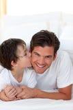 Petit garçon embrassant son père se trouvant sur le bâti Photos libres de droits