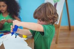 Petit garçon employant des arts et des approvisionnements de métiers images stock