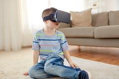 Petit garçon en casque de vr ou verres 3d à la maison Image stock