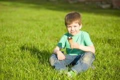 Petit garçon en parc mangeant la crème glacée  Image stock