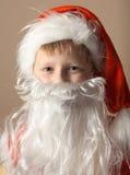 Petit garçon en procès du père noël avec la barbe Image stock