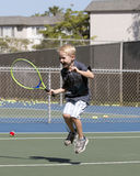 Petit garçon enthousiaste jouant le tennis Photos libres de droits