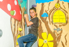 Petit garçon escaladant un mur de roche d'intérieur Photos stock