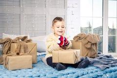 Petit garçon espiègle drôle qu'un enfant se repose sur un lit le jour de Noël avec des boîte-cadeau dans le chandail tricoté par  photo libre de droits
