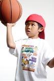 Petit garçon essayant d'équilibrer un basketbasll Image libre de droits