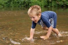 Petit garçon essayant de pêcher un poisson au milieu du courant Photos stock