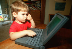 Petit garçon essayant de travailler sur l'ordinateur portable Images stock