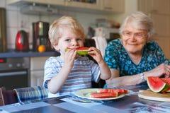 Petit garçon et arrière grand-mère d'enfant en bas âge mangeant la pastèque Photographie stock libre de droits