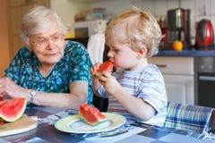 Petit garçon et arrière grand-mère d'enfant en bas âge mangeant la pastèque Photos stock