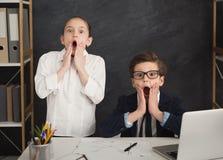 Petit garçon et fille étonnés dans le tenue de soirée au bureau photo libre de droits