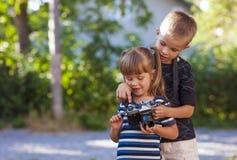 Petit garçon et fille apprenant comment employer l'appareil-photo de photo Photos libres de droits