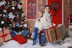 Petit garçon et fille avec des cadeaux petit garçon heureux tenant le cadeau de Noël Images stock