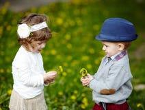 Petit garçon et fille avec des pissenlits Images stock