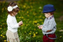 Petit garçon et fille avec des pissenlits Image stock