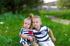 Petit garçon et fille avec l'appareil-photo se reposant sur l'herbe extérieure Photos stock