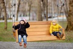 Petit garçon et fille ayant l'amusement sur l'arrière cour de jardin d'enfants Image libre de droits
