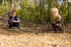 Petit garçon et fille construisant les tepees en bois Photos libres de droits