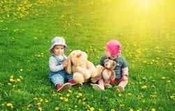 Petit garçon et fille dans des chapeaux se reposant sur le champ avec les jouets mous en été Image libre de droits