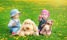Petit garçon et fille dans des chapeaux se reposant sur le champ avec les jouets mous en été Images stock