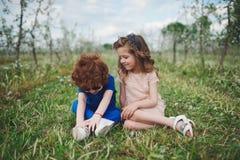 Petit garçon et fille dans le jardin de floraison Images stock