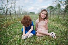 Petit garçon et fille dans le jardin de floraison Photo libre de droits