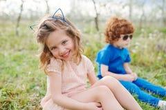 Petit garçon et fille dans le jardin de floraison Photographie stock