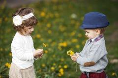 Petit garçon et fille de Cutle avec le pissenlit Images libres de droits