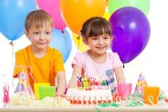 Petit garçon et fille de sourire avec le gâteau d'anniversaire et les ballons de couleur Image stock