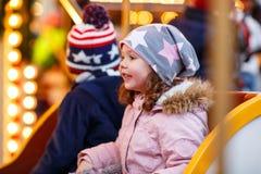 Petit garçon et fille, enfants de mêmes parents sur le carrousel au marché de Noël Images libres de droits