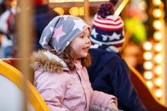 Petit garçon et fille, enfants de mêmes parents sur le carrousel au marché de Noël Photographie stock