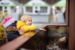 Petit garçon et fille jouant avec la fontaine de ville photographie stock libre de droits