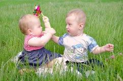 Petit garçon et fille jouant sur l'herbe verte Images libres de droits