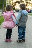 Petit garçon et fille marchant ensemble Images stock