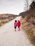 Petit garçon et fille marchant main dans la main Photographie stock libre de droits