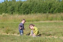 Petit garçon et fille paly sur l'herbe au pré vert Photos stock